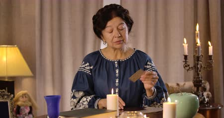 mystik : Concentrated Caucasian senior woman taking out cards from card deck and putting them on the table. Serious female fortune teller reading cards. Cinema 4k ProRes HQ. Dostupné videozáznamy