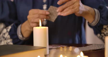 mystik : Close-up of lighting candle standing on the table as blurred female Caucasian hands taking out cards at the background. Unrecognizable female fortune teller reading cards. Cinema 4k ProRes HQ. Dostupné videozáznamy