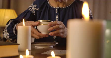 boszorkány : Female Caucasian hands raising coffee cup. Senior unrecognizable prophet reading fate on coffee grounds. Old woman telling fortune. Divination, prediction, mystery. Cinema 4k ProRes HQ. Stock mozgókép