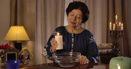 mystik : Mature Caucasian woman holding big candle and moving it around plate with water. Senior female magician performing ritual of fortune telling. Magic, fate, destiny. Cinema 4k ProRes HQ.