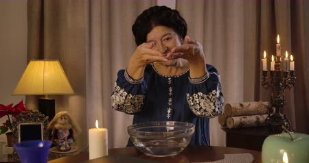 mystik : Portrait of senior Caucasian brunette woman putting hands into plate with water, looking at camera and smiling. Female fortune teller sitting at the table with lighting candles. Cinema 4k ProRes HQ.