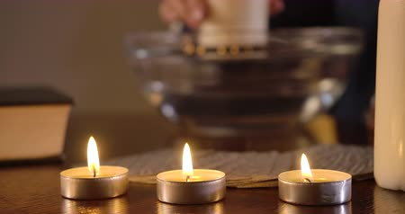 mystik : Close-up of three lighting candles standing on the table, cards lying behind. Female Caucasian hand moving big candle around plate with water at the background. Magic, augury. Cinema 4k ProRes HQ. Dostupné videozáznamy