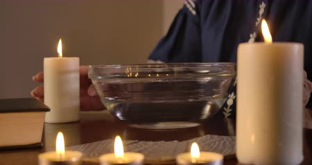 mystik : Close-up of female Caucasian hands putting plate with water on the table, taking lighting candle and moving it around liquid. Mature unrecognizable woman performing ritual. Cinema 4k ProRes HQ. Dostupné videozáznamy