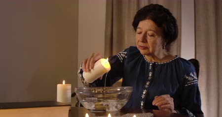 mystik : Close-up of mature Caucasian woman pouring candle wax into water. Serious female magician predicting future. Divination, mystery, ritual. Cinema 4k ProRes HQ. Dostupné videozáznamy