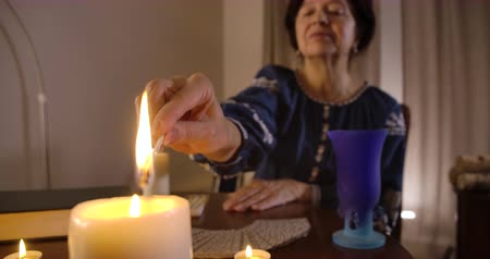 ритуал : Close-up of female Caucasian hand lighting up candle standing at the foreground. Old serious fortune teller sitting at the table at the beginning of ritual. Cinema 4k ProRes HQ.