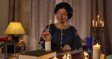 feiticeiro : Front view of smiling Caucasian brunette woman sitting at the table and lighting up candles. Senior fortune teller preparing for ritual. Card deck lying on the table face down. Cinema 4k ProRes HQ.