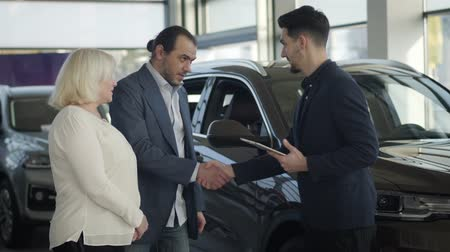 visitatori : Young Caucasian car dealer greeting visitors in dealership. Successful businessman in suit buying new vehicle for his mature blond mother. Business, automobile industry, lifestyle.