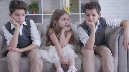 nuda : Caucasian twin brothers sitting on couch on both sides of cheerful cute girl. Portrait of bored children resting indoors. Friendship, childhood, leisure, lifestyle. Dostupné videozáznamy