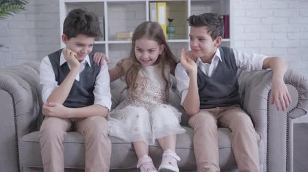 identical : Portrait of cheerful brunette Caucasian girl sitting on couch and shaking twin brothers shoulders. Positive little pretty child having fun with siblings indoors. Joy, happiness, lifestyle.