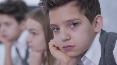 identical : Close-up face of handsome little Caucasian boy looking at camera. Portrait of bored brunette guy sitting with twin brother and sister at home. Lifestyle, childhood, leisure. Stock Footage