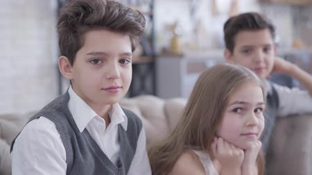 identical : Close-up portrait of nice Caucasian brunette boy posing indoors as his twin brother and cute little sister sitting at the background and looking at camera. Happy children resting at home. Stock Footage