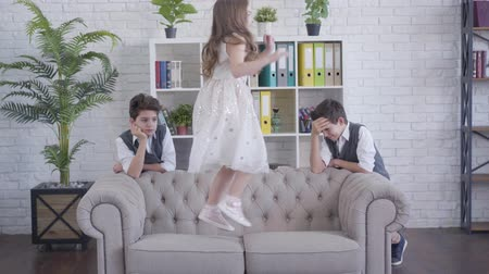 boring : Exhausted twin brothers standing on both sides of sofa and watching their cheerful sister jumping on couch. Tired siblings spending time with younger brunette girl indoors. Lifestyle, unity, family.