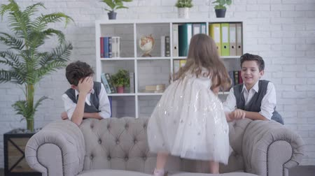 identical : Little cheerful Caucasian girl jumping on couch and stretching boys hand. Joyful sister entertaining bored twin brothers. Lifestyle, having fun, leisure.