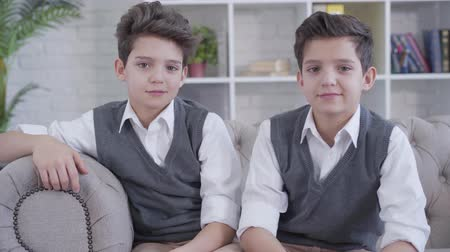 podobný : Portrait of identical twin brothers looking at each other, turning to camera and smiling. Elegant Caucasian children in similar clothes sitting on couch indoors. Family, unity, lifestyle. Dostupné videozáznamy
