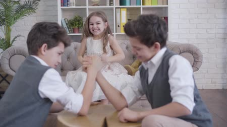 ツイン : Portrait of joyful Caucasian little girl cheering on couch as blurred twins competing in armwrestling at the foreground. Sister having fun with brothers indoors. Family, joy, leisure, lifestyle. 動画素材