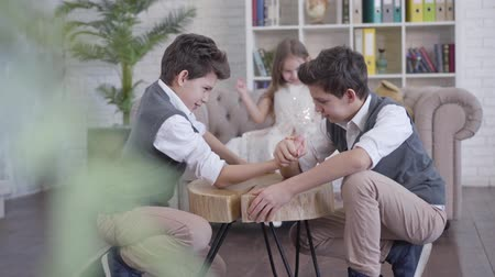 identical : Two identical twin brothers competing in armwrestling and talking as their little sister cheering at the background. Happy children enjoying free time at home. Shooting from behind house plant. Stock Footage