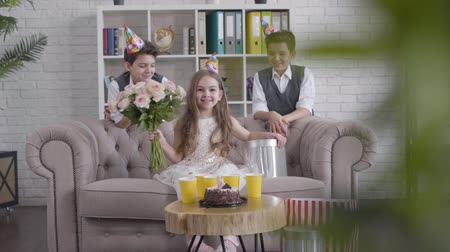 identical : Long shot, two stylish twin brothers giving bouquet of flowers and gift to happy brunette Caucasian girl. Pretty sister smelling roses and smiling as sitting on couch. Birthday, party, joy. Stock Footage