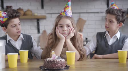 identical : Twin brothers shaking shoulders and caressing hair of sad Caucasian girl in party hat. Upset child sitting at the table with siblings celebrating birthday. Sadness, celebration, care, unity.