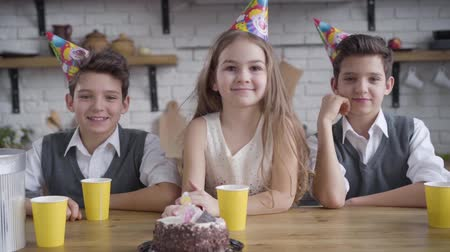 identical : Slow motion, two Caucasian twin boys and cute girl in party hats sitting at the table with birthday cake, looking at camera, talking and smiling. Camera approaching to happy children celebrating.