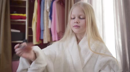 inspirar : Portrait of smiling blond Caucasian girl doing makeup indoors. Cute cheerful child applying face powder and eye shadows. Beauty, fashion, childhood. Stock Footage