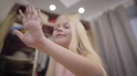 polegar : Satisfied blurred Caucasian girl looking at nails and smiling. Stylish blond child blowing on fingers with nail polish. Beauty, style, fashion. Focused on kids hand. Vídeos