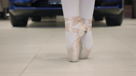 balerína : Close-up of ballet dancers feet, professional ballerina balancing on tiptoes and spinning. Car standing at the background. Art, elegance, automobile industry.