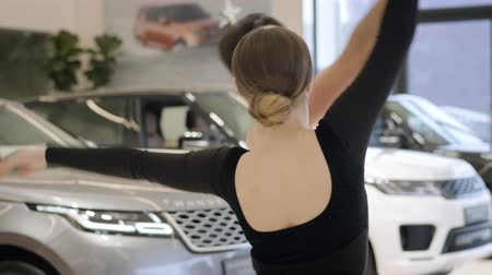 vyvažování : Portrait of Caucasian man and woman dancing ballet in car dealership. Young male and female ballet dancers performing between automobiles in showroom. Lifestyle, classic dances, auto industry.