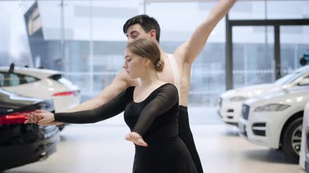 kiegyensúlyozó : Portrait of two positive Caucasian ballet dancers performing classic dance moves and looking at camera. Man and woman dancing in car dealership. Automobile industry, art, elegance.
