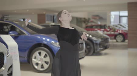 balerína : Young beautiful Caucasian ballet dancer dancing emotionally and spinning in front of row of cars. Elegant woman in black dress performing classic dance in auto dealership. Art, elegance, lifestyle.
