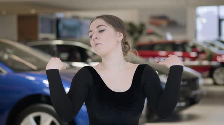 gururlu : Close-up of brunette Caucasian woman bending and spinning in car dealership. Confident young ballet dancer dancing in auto showroom. Automobile industry, elegance, art.