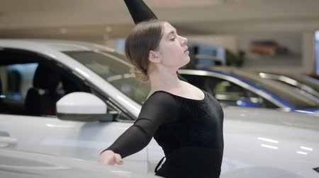 balerína : Side view of Caucasian ballerina bending back and leaving the shot. Professional female ballet dancer dancing in car showroom. Automobile industry, elegance, beauty, art.