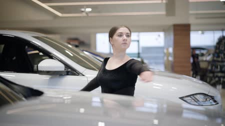 balerína : Confident Caucasian woman spinning on tiptoes between white cars in auto showroom. Beautiful female ballet dancer practicing in car dealership. Elegance, art, lifestyle.