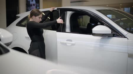 balerína : Cute Caucasian ballerina coming to the car, bending back, opening door and sitting inside. Portrait of graceful female ballet dancer dancing in car dealership. Beauty, elegance, art. Dostupné videozáznamy