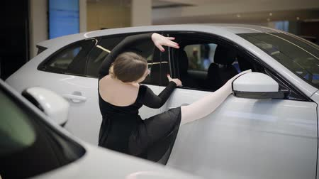dans : Back view of young female ballet dancer putting leg on car window sill and making classic dance moves. Graceful confident woman dancing in auto dealership. Automobile industry, art, elegance. Stok Video