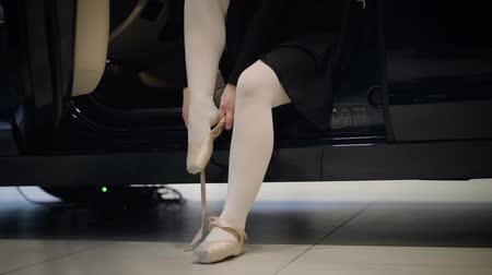 balerin : Unrecognizable Caucasian ballet dancer putting on pointes as sitting on drivers seat in car. Elegant woman tying up ballet shoes. Choreography, art, automobile industry.