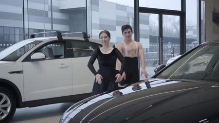 kiegyensúlyozó : Cheerful Caucasian man and woman dancing ballet in car dealership, slowmo. Male and female ballet dancers moving in auto showroom. Automobile industry, art, elegance. Slow motion.