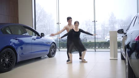 vyvažování : Long shot of young Caucasian ballet dancers dancing in car dealership. Man and woman performing classic dance in auto showroom. Art, elegance, lifestyle. Slow motion.