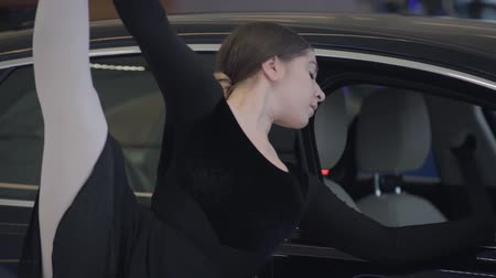 balerína : Charming Caucasian female ballet dancer standing with leg up in car dealership. Portrait of professional ballerina next to black car. Auto industry, art, beauty, elegance. Dostupné videozáznamy