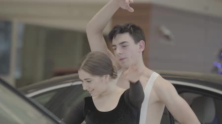 vyvažování : Slowmo dance of young Caucasian ballet dancers in car showroom. Camera following moves of man and woman dancing in auto showroom. Automobile industry, elegance, art, grace. Dostupné videozáznamy