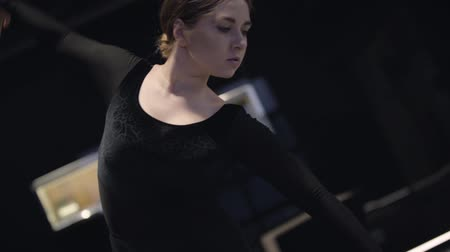 balerína : Portrait of female Caucasian ballet dancer moving hands up and down. Beautiful young woman dancing in darkness. Art, lifestyle, elegance. Slowmo.