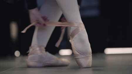 balerína : Slowmo of graceful unrecognizable Caucasian ballerina tying up pointes. Elegant female ballet dancer putting on ballet shoes. Grace, choreography, elegance, art.