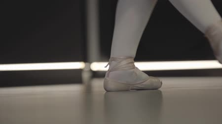 balerína : Elegant ballerina moving feet together and standing up on tiptoes. Close-up of ballet dancers feet in pointes. Grace, art, elegance, choreography. Dostupné videozáznamy