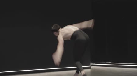 vyvažování : Portrait of professional Caucasian ballet dancer jumping up, spinning in air, and standing on one knee. Confident young man dancing classic dance in stage light. Slow motion.