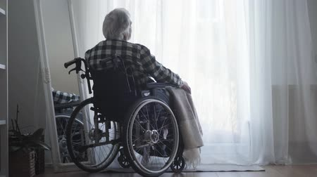 think big : Back view of old Caucasian man sitting in wheelchair in front of big window closed with curtain and thinking. Lonely elderly man spending day alone at home. Oldness, retirement, disabled people.