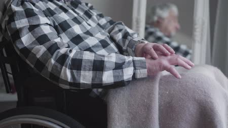 mansão : Camera approaching to unrecognizable mans hands shaking. Elderly disabled man sitting in wheelchair and reflecting in mirror at the background. Illness, disability, oldness. Stock Footage