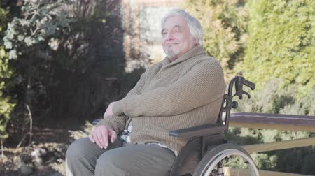 inwalida : Portrait of smiling old Caucasian disabled man sitting on wheelchair and looking away. Elderly retiree in warm clothes spending sunny day outdoors. Lifestyle, happiness, enjoyment, disability.