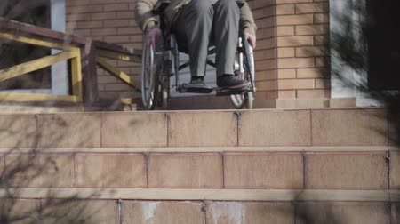 oportunidade : Unrecognizable elderly Caucasian man in wheelchair rolling to stairs and stopping. Disabled person having no opportunity to roll down. Ramp availability, disability problems.