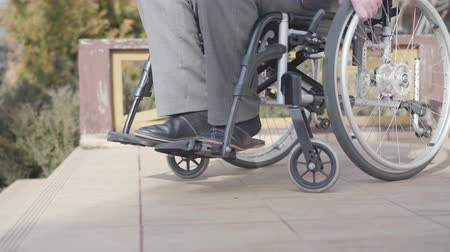 no ramp : Side view close-up of wheelchair with unrecognizable old man rolling to stairs. Concept of ramp availability, disability challenges, lifestyle.
