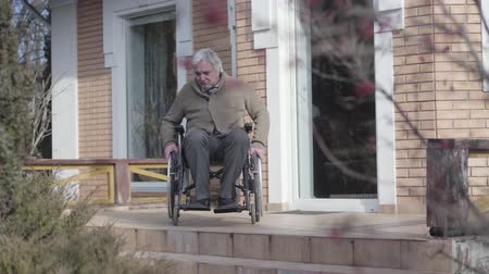 impaired : Old Caucasian man in wheelchair rolling to stairs without ramp outdoors and throwing up hands in frustration. Disabled retiree having no motion availability. Concept of disability, problem, challenge. Stock Footage