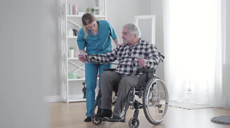 invalidní vozík : Long shot of concentrated Caucasian woman helping old man to stretch elastic band. Mature retiree exercising with the assistance of invalid tender in nursing home. Rehabilitation, physical therapy.